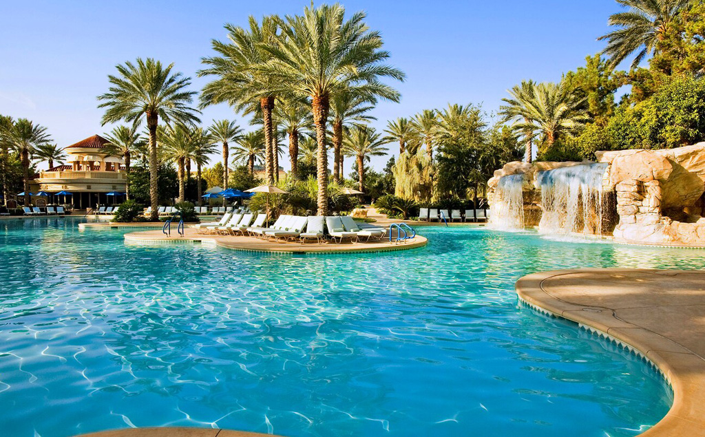 JW Marriott Las Vegas pool with waterfall, lounge chairs, and palm trees